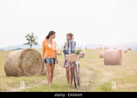Friends with bicycle walking on field, Roznov, Czech Republic - Stock Photo