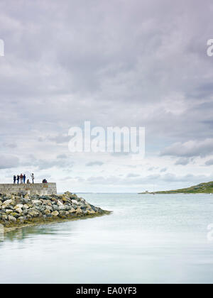 Group of people standing on harbor wall, Howth, Dublin Bay, Republic of Ireland - Stock Photo