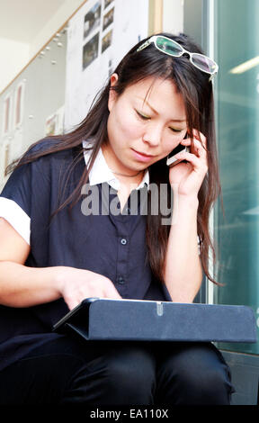 Female architect using smartphone and digital tablet on office step - Stock Photo