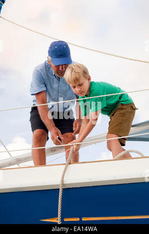 Boy helping grandfather pull ropes on sailboat - Stock Photo