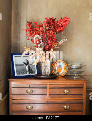 Dried flowers and a family photo on old wooden chest of drawers - Stock Photo