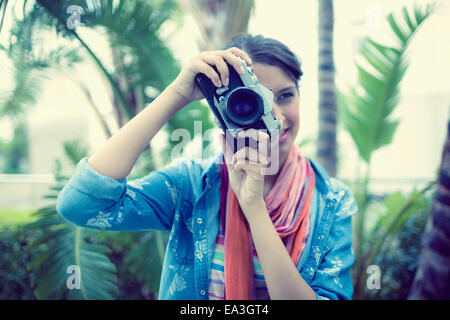 Smiling brunette taking a photo outside - Stock Photo