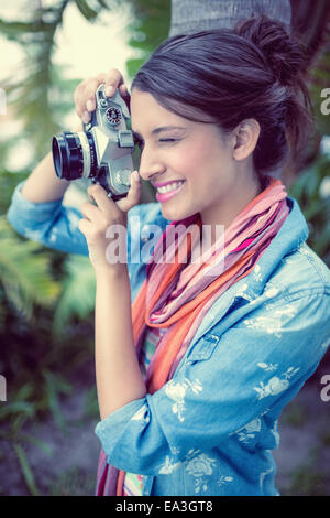 Cheerful brunette taking a photo outside - Stock Photo