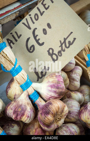 Bunch of pink garlic on sale at a local market in France, Europe. - Stock Photo
