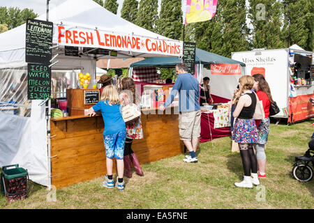 People wait in line for drinks at a homemade lemonade stall at an English summer fair. - Stock Photo