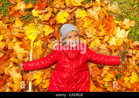 Happy girl laying on the autumn leaves with rake - Stock Photo