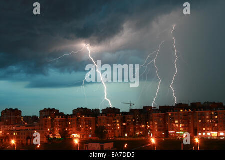 Lightning over night city during a lightning storm - Stock Photo