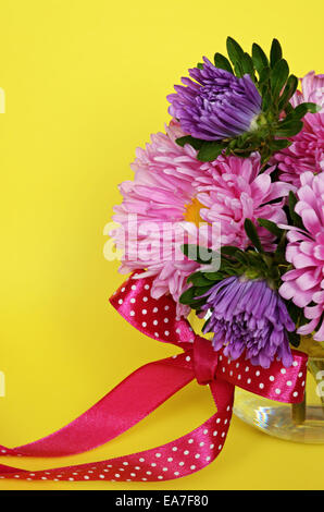 Asters and red bow on yellow background - Stock Photo