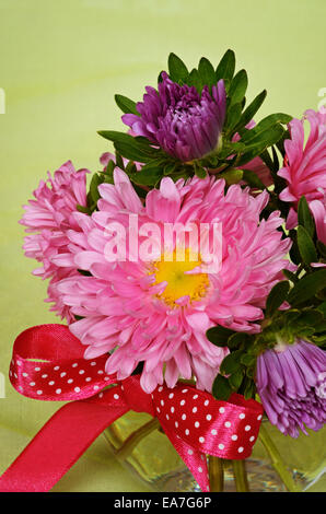 Bouquet of asters in a glass vase on green background - Stock Photo
