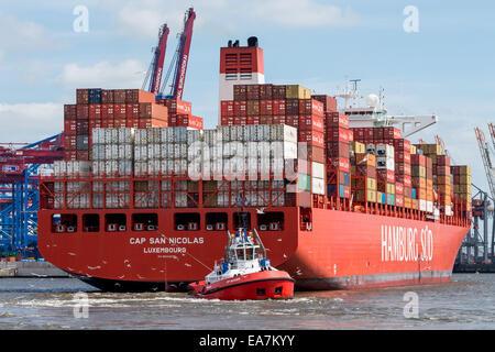 Hamburg, Germany - June 23, 2014: Tug boat pulls large container ship in the port of Hamburg - Stock Photo