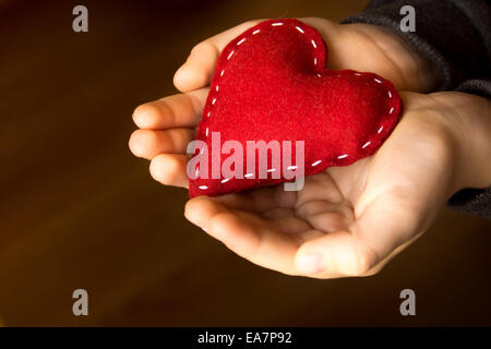 Red heart in child hands, hand made gift, valentine day and family love concept, close up, horizontal - Stock Photo