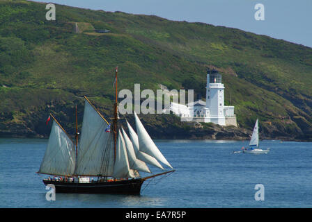 St Mawes tall ship leaving the Carrick Roads sailing past the St Anthony Head Lighthouse Falmouth Carrick Mid Cornwall - Stock Photo