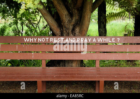 Bench seat with 'why not rest and pray a while?' carved into it at St Joseph's Catholic church in Jerusalem, New - Stock Photo