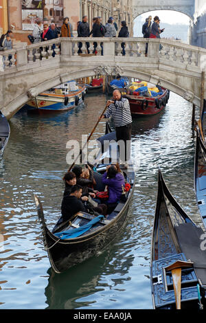 Japanese tourists in a gondola on a canal in Venice, Italy. - Stock Photo