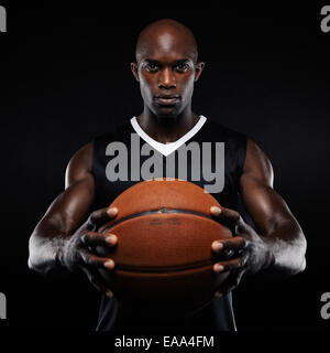 Portrait of muscular young male basketball player with a basketball posing on black background. Afro american male - Stock Photo