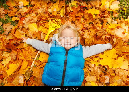 Happy blond boy laying on the autumn leaves - Stock Photo