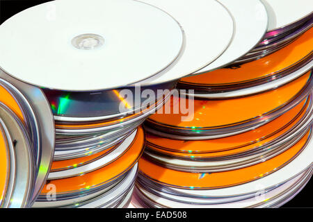 Closeup view of a collection of many colorful stacked compact disks in a row - Stock Photo