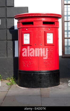 Large red traditional Royal Mail pillar box with two letter box openings, Royal Wootton Bassett, Wiltshire, England, - Stock Photo