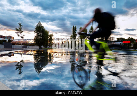Cyclist passing by the pools and fountains in Madrid Rio Park. Madrid. Spain - Stock Photo