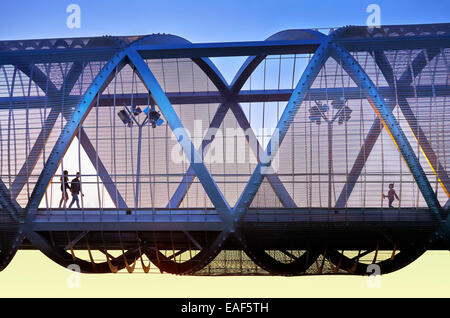 People passing by the Arganzuela bridge, designed by architect Dominique Perrault. Madrid Rio Park. Madrid. Spain - Stock Photo