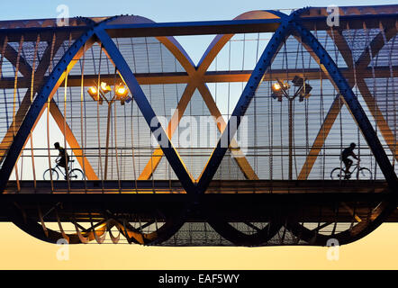 Two cyclists passing by the Arganzuela bridge, designed by architect Dominique Perrault. Madrid Rio Park. Madrid. - Stock Photo
