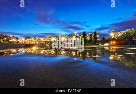 The sun sets over the Arganzuela bridge, designed by architect Dominique Perrault. Madrid Rio Park. Madrid. Spain - Stock Photo