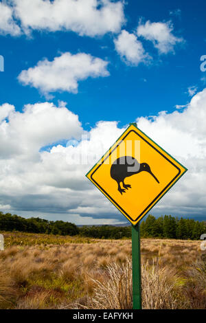 Kiwi crossing road sign against cloudy sky at New Zealand - Stock Photo