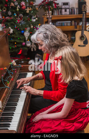 An Older Woman Showing A Six Year Old Girl How To Play The Piano, Formal Dress, House Decorated For Christmas. - Stock Photo