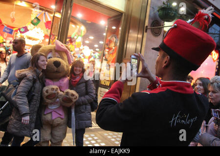 London, UK 16 November 2014.  A Hamleys shop assistant takes photos of people outside the main Regent Street entrance.Thousands - Stock Photo