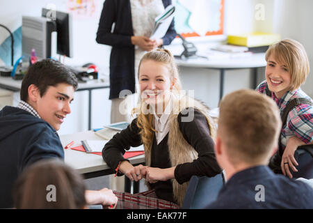 High School students sitting and smiling in classroom - Stock Photo