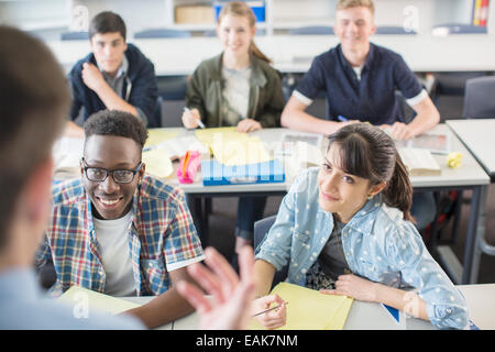Cheerful High School students sitting in classroom - Stock Photo