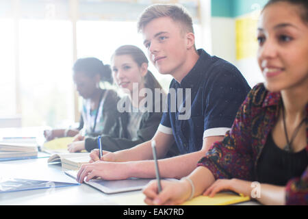 Students sitting in classroom during lesson - Stock Photo