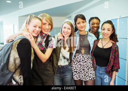 Group portrait of cheerful female students standing in locker room - Stock Photo