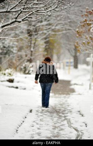 A woman in London, Ontario walks down a snowy winter street. - Stock Photo
