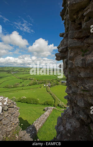 Spectacular view of vast emerald farmlands on rolling hills under blue sky from ruins of hilltop Carrig Cennen castle - Stock Photo