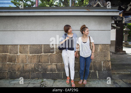 Two women standing outdoors, leaning against a wall. - Stock Photo