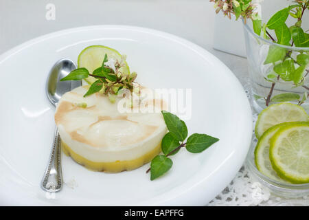 Delicious dessert of lemon pie, table set, decorated with flowers - Stock Photo