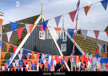 Traditional wooden houses decorated with flags of Dutch national colors for Koningsdag, or King's Day, Marken, North - Stock Photo