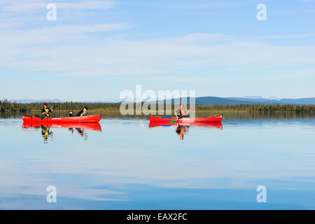 Two people canoe on a quiet lake - Stock Photo