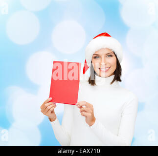 smiling woman in santa hat with greeting card - Stock Photo