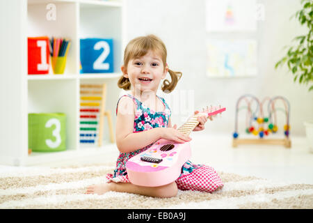 little girl playing guitar - Stock Photo