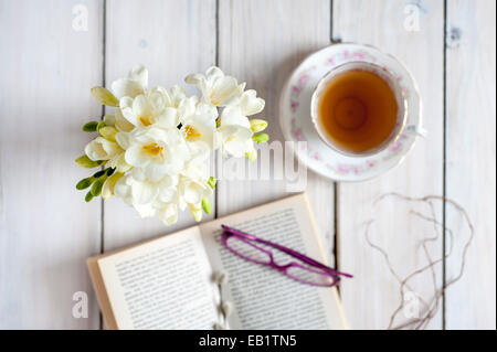 tea time - tea served in vintage teacup with posy of white freesias, book and glasses - Stock Photo