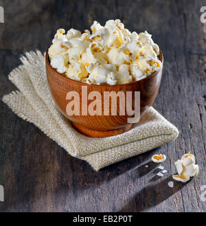 Fresh popcorn in bowl on old wooden table, isolated - Stock Photo