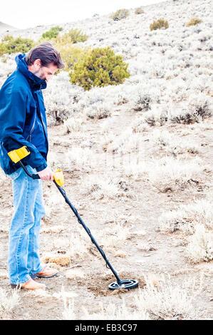 Man using metal detector in Black Rock desert, Nevada, America, USA - Stock Photo