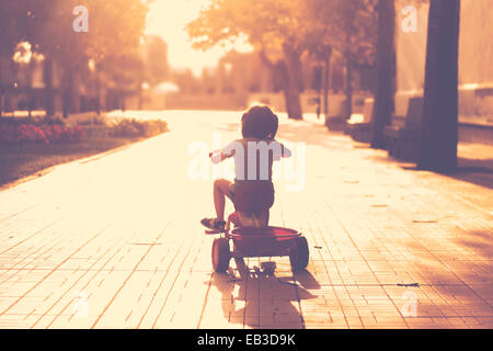 Little girl(2-3) on tricycle in park - Stock Photo