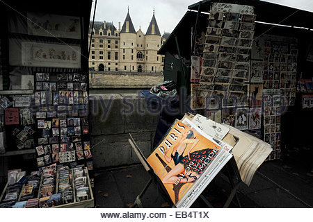 The Conciergerie  looms behind poster and postcard vendors on the bank of the Seine River. - Stock Photo