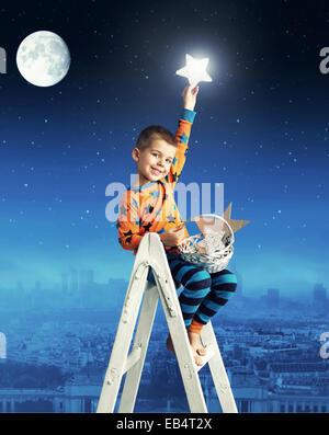 Little man collecting shining stars - Stock Photo