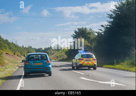 A police car overtakes traffic with emergency blue lights flashing on a Uk road - Stock Photo