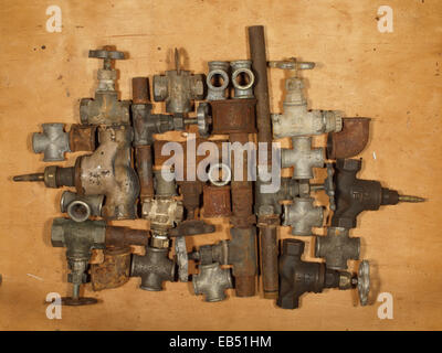 Various old and rusty fittings and valves arranged on a wooden table. - Stock Photo