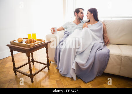 Cute couple relaxing on couch under blanket - Stock Photo